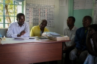 Gumbwa Primary School headman discusses the Solar PV project with the energy committee