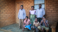 Teacher and is family who now have a solar home system as part of the